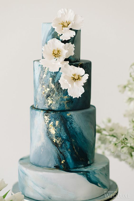 a blue marble wedding cake is topped with gilded flowers that pick up on the subtle gold flecks