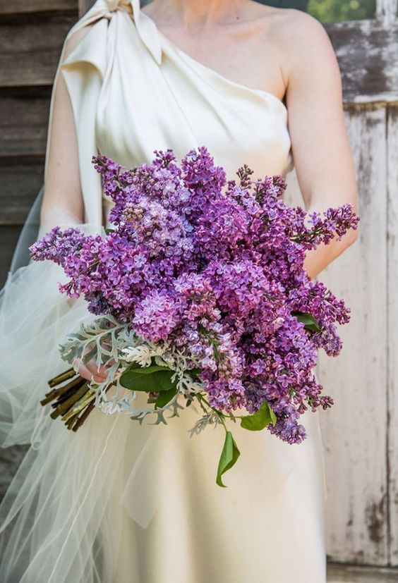 a lush violet lilac wedding bouquet with pale miller and greenery for a spring bride