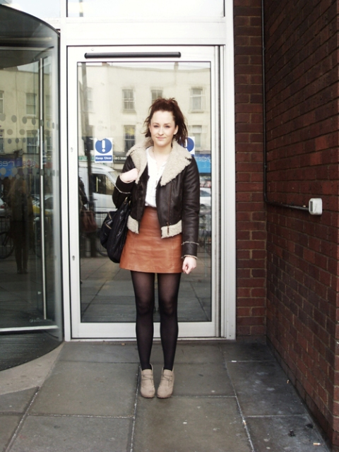 With white shirt, leather skirt, shearling jacket and black bag