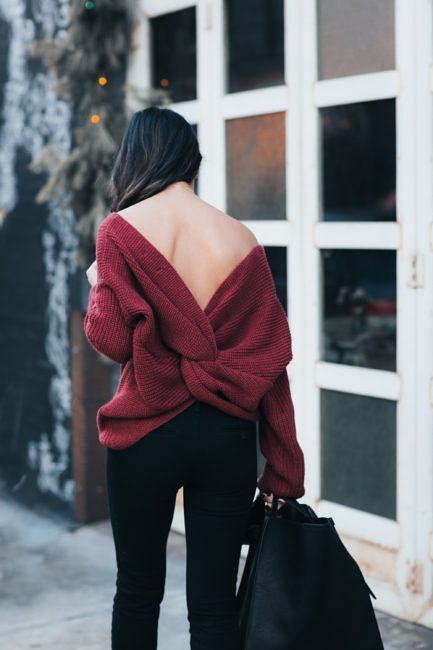 black jeans, a maroon cutout back sweater with a knot