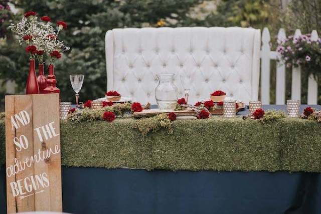 The wedding tables were covered with moss, with red blooms, baby's breath and wooden touches to give it a rustic feel