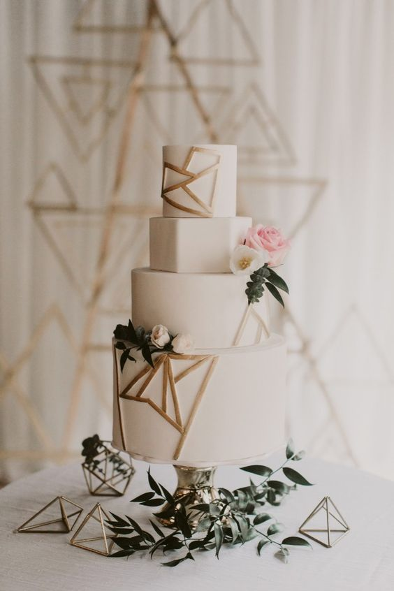a white wedding cake with geometric layers and gold geometric details