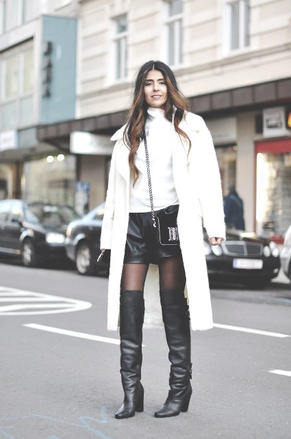 With white turtleneck, white midi coat, black over the knee boots and chain strap bag