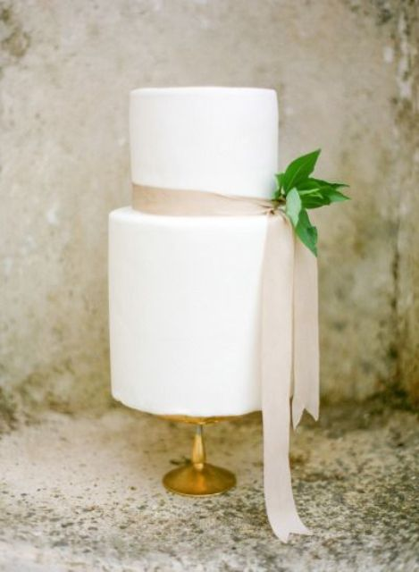 a white wedding cake with a blush ribbon and foliage for a cute and chic look