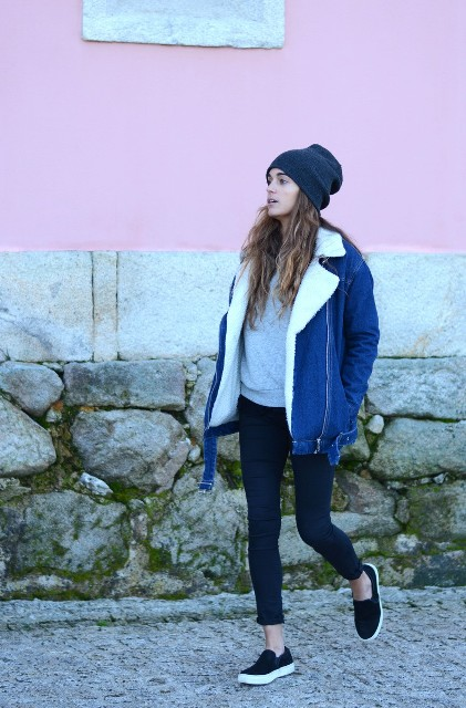 With gray sweatshirt, crop jeans, black shoes and navy blue beanie