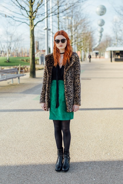 With black shirt, green skirt and black leather boots