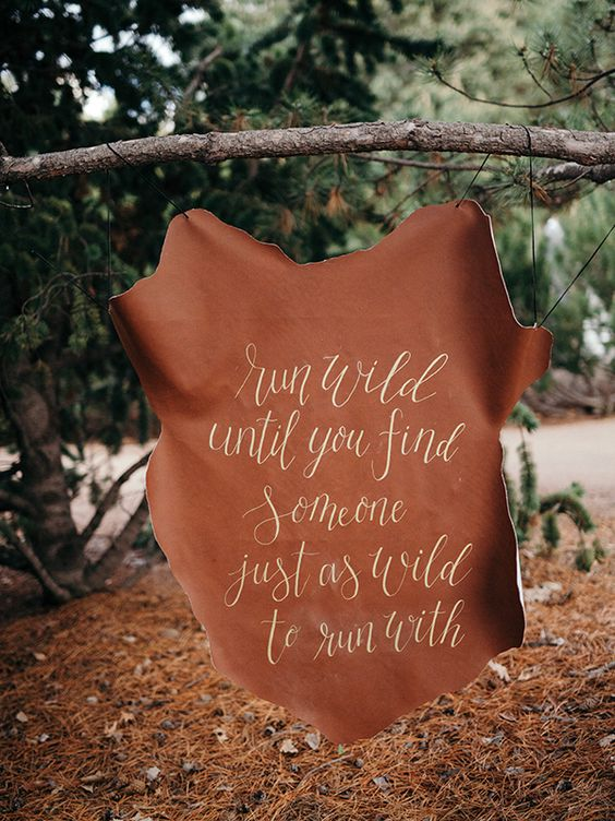 a hand lettered leather sign for an outdoor rustic, camping or woodland wedding