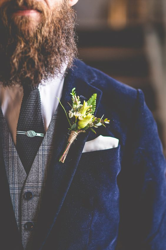 a hipster groom look with a navy velvet jacket, a tweed vest, a white shirt and a black tie