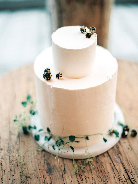 a simple frosted cake decorated with gilded berries and greenery