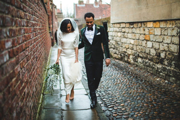 an edgy modern groom's look with black trousers, a white shirt, an emerald velvet jacket and a matching bow tie