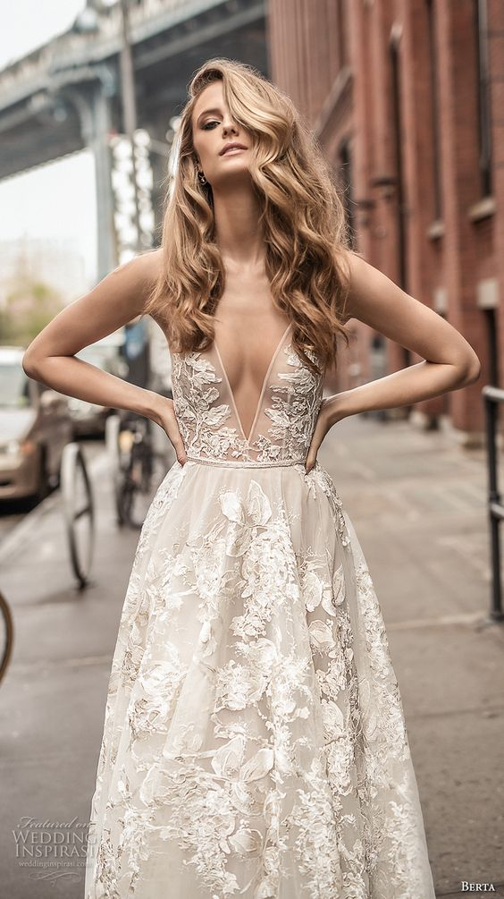 a wedding gown with a plunging neckline, a full skirt, and lace appliques all over the dress