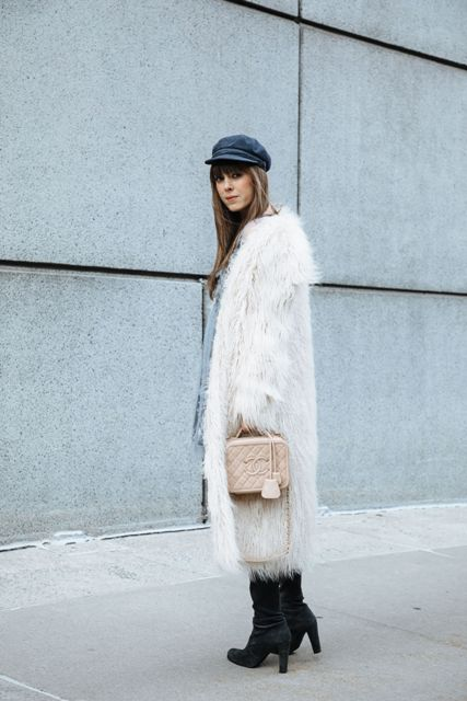 With dress, boots, faux fur coat and beige bag