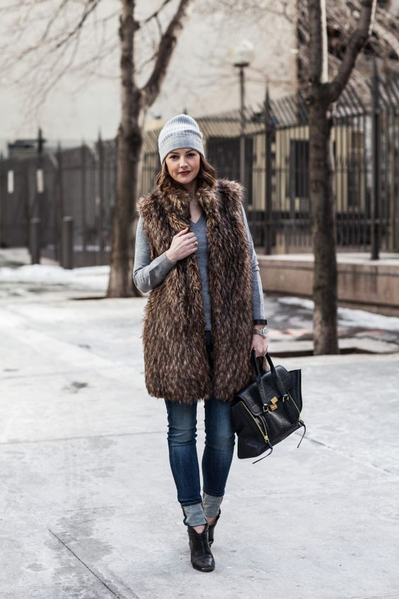 blue jeans, a grey top, black booties, a grey beanie and a long fur vest