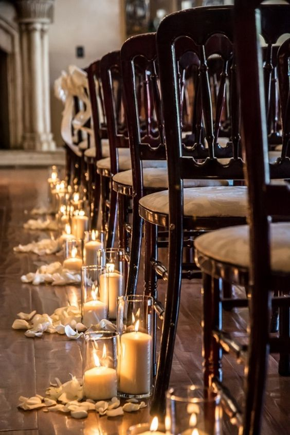 candles in tall vases and petals are a timeless idea for lining the aisle and they will fit most of wedding styles