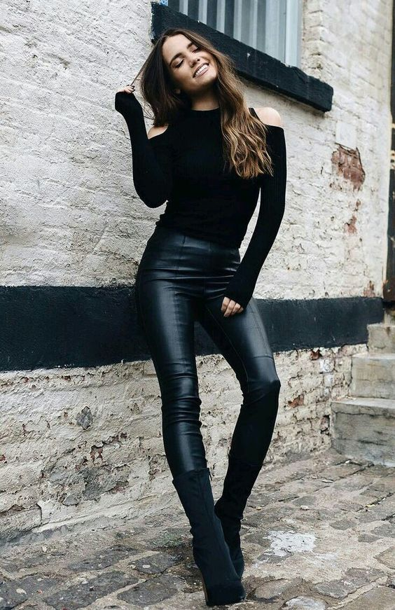 a black cold shoulder sweater, black leather pants and black suede booties
