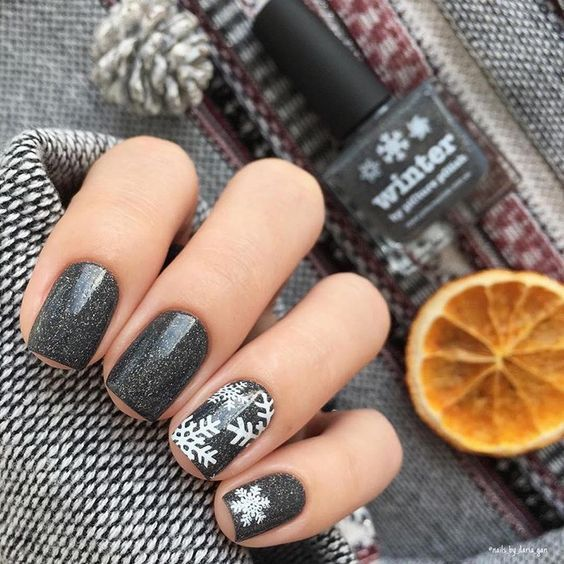 black glitter nails with some snowflakes look very chic