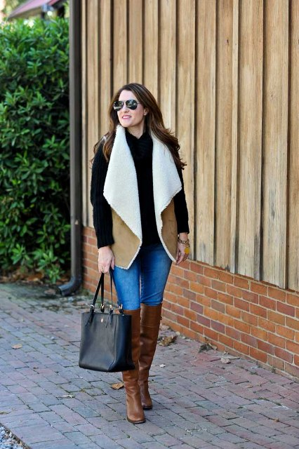 With black sweater, skinny jeans, brown boots and black tote