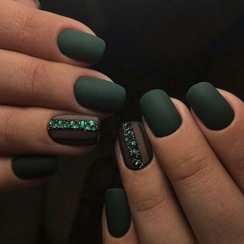 matte dark green nails with an accent nail lined up with emerald rhinestones