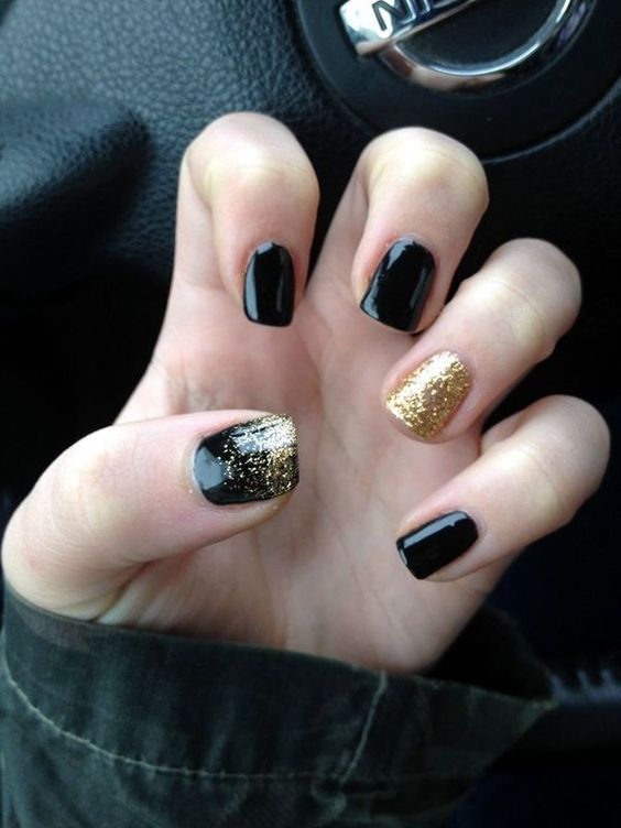 black nails with a gold glitter accent nail and a touch of glitter