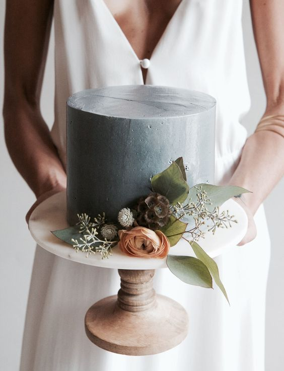a concrete-inspired round wedding cake with blooms and foliage looks romantic and modern