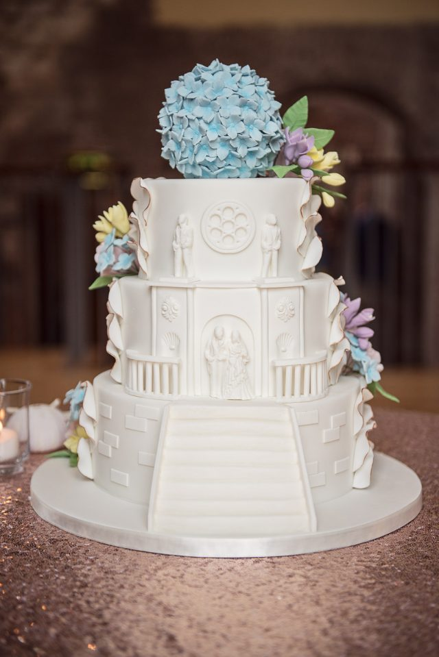 The wedding cake was a white one, with the pirate castle theme, and decorated with pastel sugar flowers