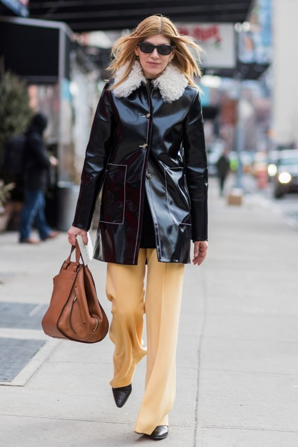 With light yellow pants, black boots and brown bag