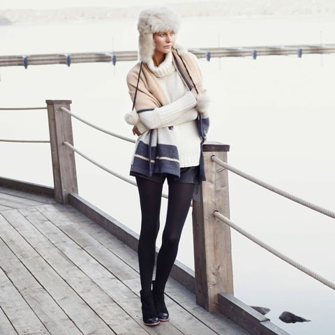With white sweater, black tights, black shorts, ankle boots and scarf