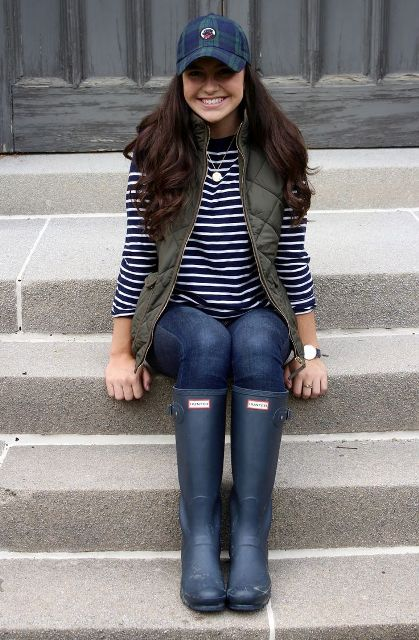 With striped shirt, olive green puffer vest, jeans and high boots