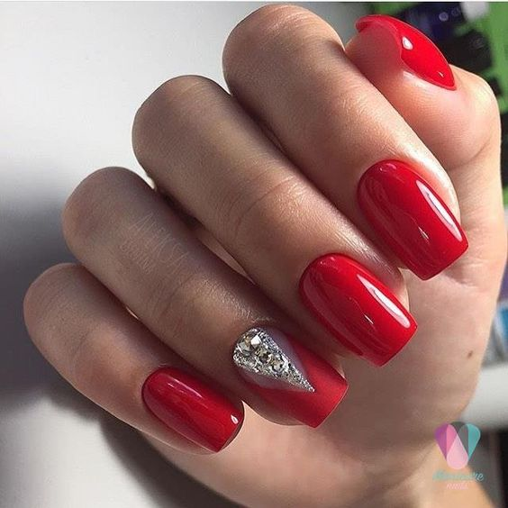 a classic red manicure spruced up for the holidays with a rhinestone accent
