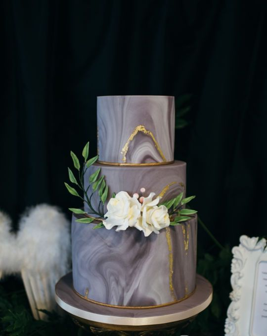 a grey marbleized wedding cake with gold leaf and white blooms for detailing