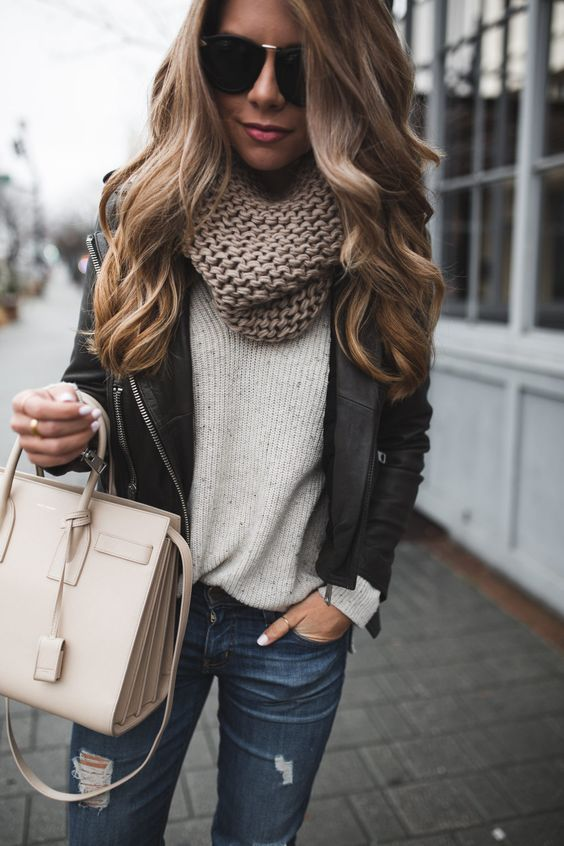 jeans, a neutral sweater, a chunky knit scarf and a black leather jacket