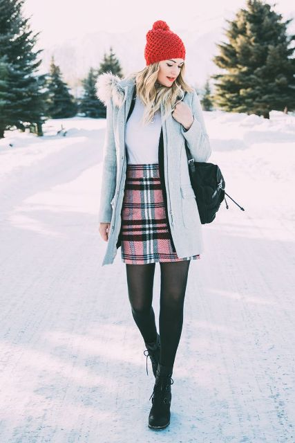 With shirt, lace up boots, light blue coat and red beanie
