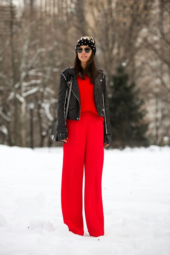 red wide pants, a red sweater, a black leather jacket and an embellished beanie