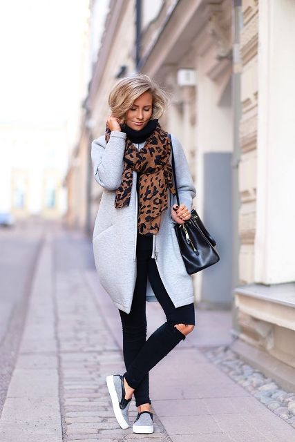 With light blue coat, distressed jeans, shoes and black bag