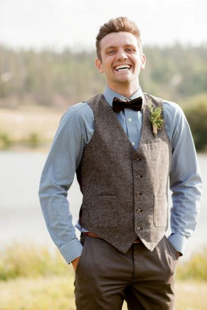a blue printed button down, tweed vest, brown dress pants, and dark bow tie for a vintage and rustic look