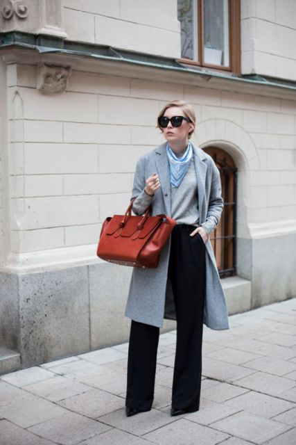 With gray shirt, gray knee-length coat, wide-leg pants and red bag