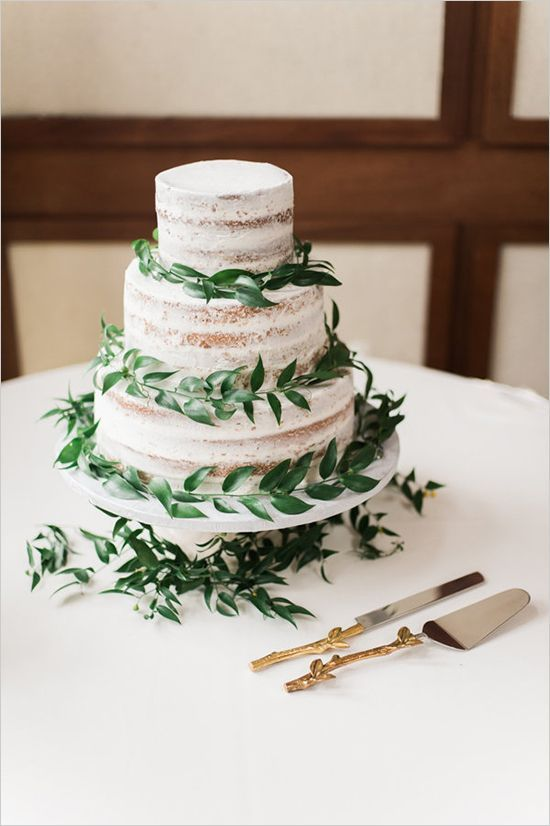 a naked wedding cake with fresh greenery is all you need for a fresh sprign look