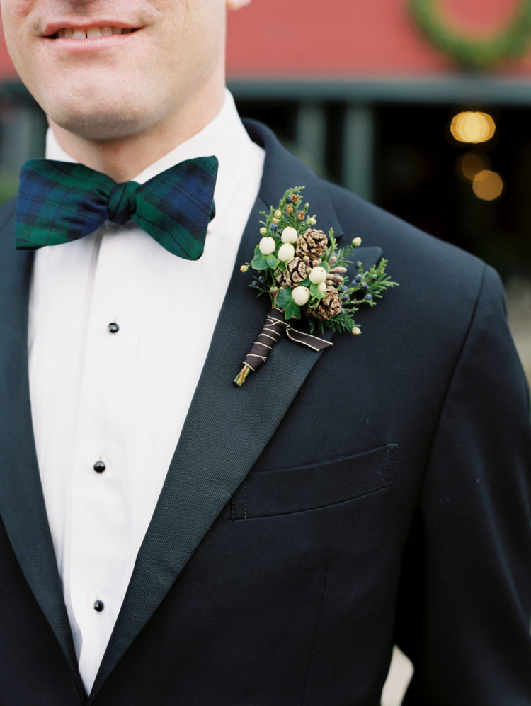 The groom was wearing a black tux with a black watch tartan bow tie and a bold boutonniere