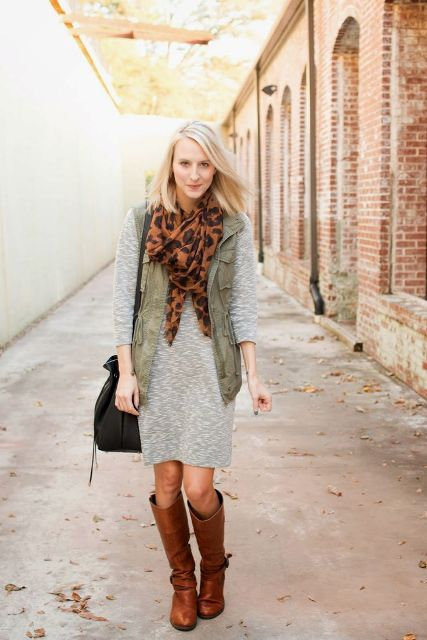 With gray dress, high boots, vest and black bag