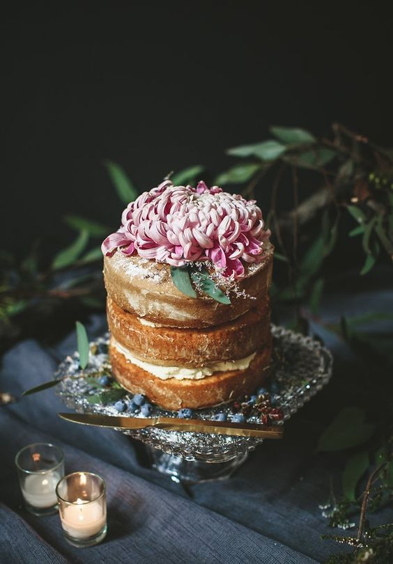a tall yet small naked wedding cake topped with a single large bloom in pink looks elegant