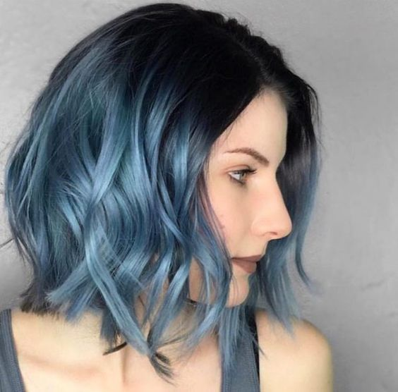 a black roots and metallic blue ombre with waves
