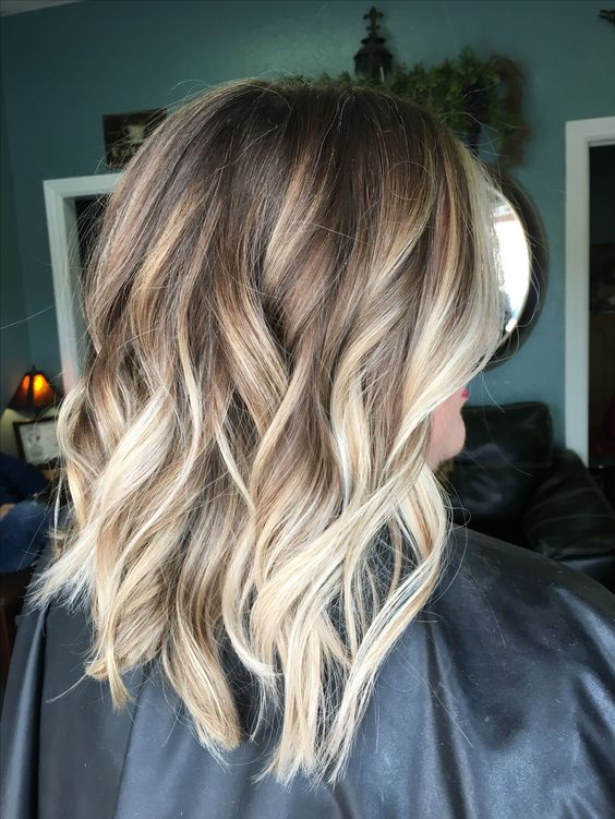 light brown wavy and layered hair with blonde balayage looks chic and fun