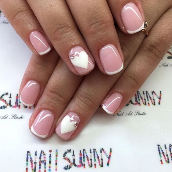 French manicure with white nail hearts topped with rhinestones for a stylish look