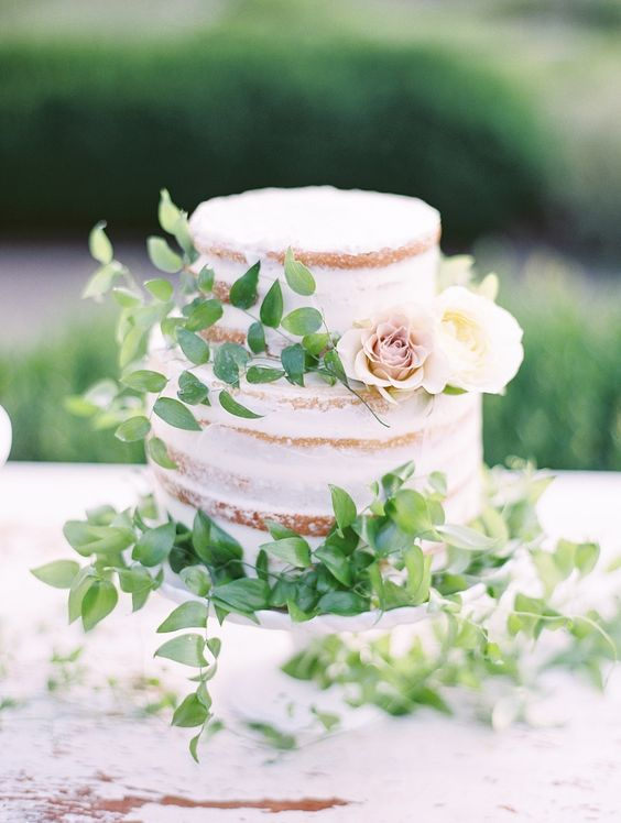 a naked cake with fresh foliage and a couple of neutral blooms for decor