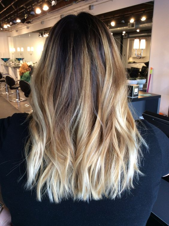 dark brown roots and intensive balayage in the shades of blonde for a bold and eye-catchy look