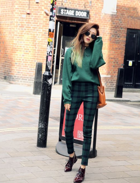 With green loose sweatshirt, brown bag and leather boots