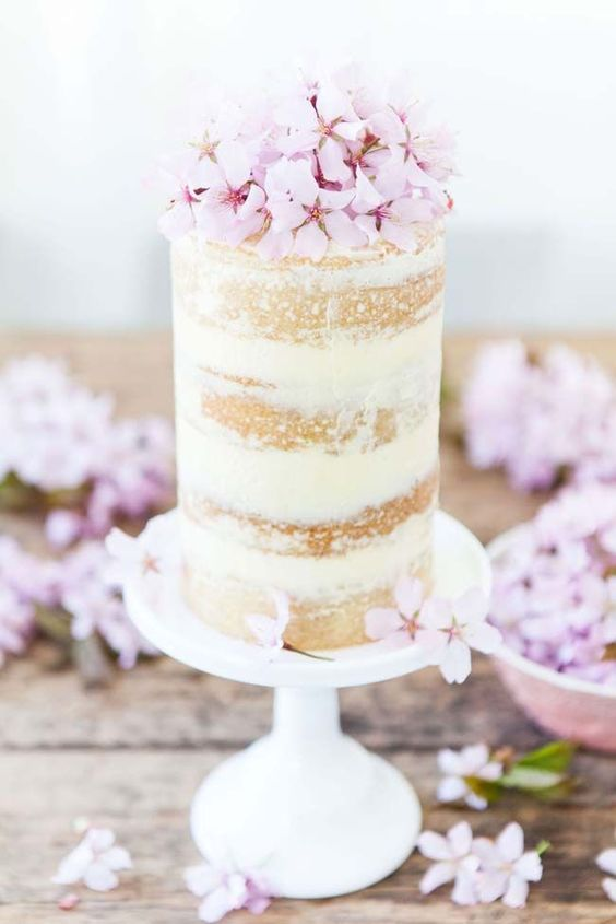 a tall and small wedding cake topped with pink cherry blossom