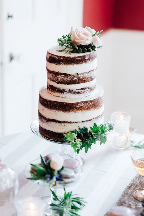 a naked wedding cake topped with blush blooms, blackberries and fresh greenery