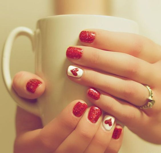 red glitter manicure with an accent white and red glitter heart nail
