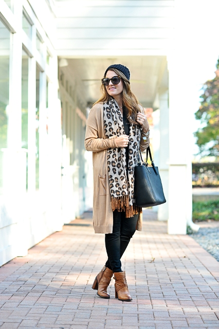 With beanie, beige cardigan, skinny pants, brown ankle boots and black tote